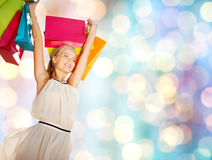 Young happy woman with shopping bags over lights Royalty Free Stock Photos