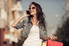 Young happy woman with shopping bags walking on street. Royalty Free Stock Photo