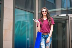 Young happy woman with shopping bags walking on street stock image