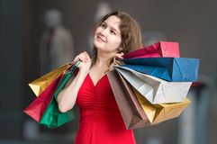Young happy woman is shopping and holds many colorful bags in hands.  royalty free stock photos
