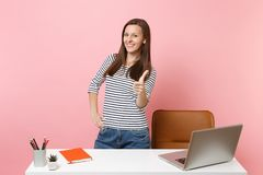 Young happy woman showing thumb up, work and standing near white desk with contemporary pc laptop isolated on pastel. Pink background. Achievement business stock photos