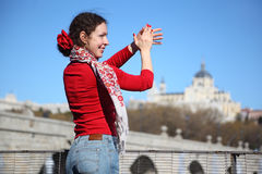 Young happy woman shows flamenco gesture near bridge. Of Segovia in Madrid, Spain royalty free stock photography