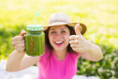 Young happy woman showing thumbs up with green smoothies at a picnic. Healthy food, detox and diet concept. Young happy woman shows on green smoothies at a Royalty Free Stock Photo