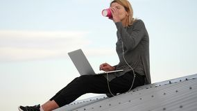 Young woman sits with laptop and listening music on headphones on the rooftop.