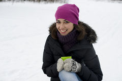 The young happy woman sits on snow with hands a cu Royalty Free Stock Photo