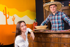 Young happy woman sitting at the bar counter next to the bartend. Young happy women sitting at the bar counter next to the bartender wearing sombrero and a plaid royalty free stock images