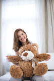 Young happy woman sitting on the bed Stock Photos