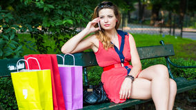 Young happy woman sitting on a bench with colorful shopping bags and mobile phone. Stock Photos