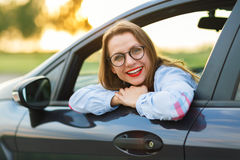 Young happy woman sitting in a car. Concept of buying a used car or a rental car Royalty Free Stock Image
