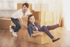 The young happy woman sitting in a cardboard box. Moving, purchase of new habitation. The young happy women sitting in a cardboard box. Moving, purchase of new Stock Photo