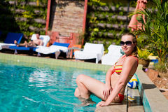 Young Happy woman sitting close to pool Royalty Free Stock Photography