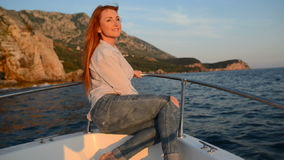 Young happy woman sitting in going cutter looks at adriatic sea. Red-haired woman sits on deck of a boat during a sea walk along the Adriatic coast, slow motion stock video