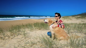 Young happy woman sitting with Golden Retriever dog on the beach stock footage