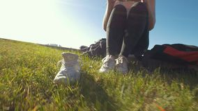 Young happy woman sitting on the grass with young man and changes her sneakers in sunny day. Slow motion stock video footage
