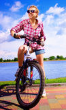 Young happy woman is sitting on her bicycle Royalty Free Stock Image