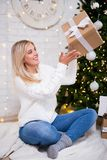 Young happy woman sitting in living room with decorated Christma stock images
