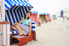 Young happy woman sitting and relaxing on beach chair on the bea Royalty Free Stock Photo