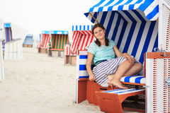 Young happy woman sitting and relaxing on beach chair on the bea Stock Images