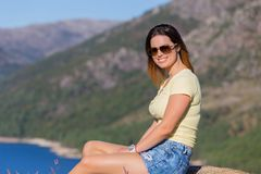 Girl enjoying the lake. Young happy woman sitting on the rock mountain, relaxing and enjoying the lake at Geres, Portuguese National Park royalty free stock photo