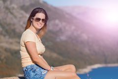 Girl enjoying the lake. Young happy woman sitting on the rock mountain, relaxing and enjoying the lake at Geres, Portuguese National Park stock photography