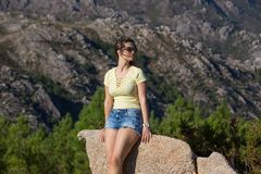 Girl enjoying. Young happy woman sitting on the rock mountain, relaxing and enjoying the valley view at Geres, Portuguese National Park royalty free stock images