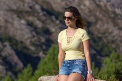 Girl enjoying. Young happy woman sitting on the rock mountain, relaxing and enjoying the valley view at Geres, Portuguese National Park stock photos
