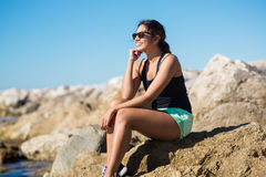 Young happy woman sitting on seaside rock smiling. Portrait of young happy woman sitting on seaside rock smiling Stock Image
