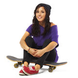 Young happy woman sitting on a skateboard Royalty Free Stock Photos
