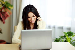 Young happy woman sitting at the table with laptop Stock Image
