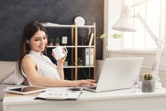 Young woman working on laptop and consulting on phone. Young happy woman sitting at the table, working on laptop, listening music with closed eyes and drinking Royalty Free Stock Photography