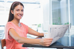 Young happy woman smiling at the camera while holding the newspaper. In the cafe Royalty Free Stock Image