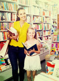 Young happy woman with smiling girl in bookstore Royalty Free Stock Photos