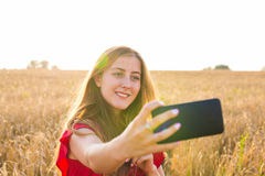 Young happy woman smiling while taking selfie picture with mobile phone in the field Royalty Free Stock Photos