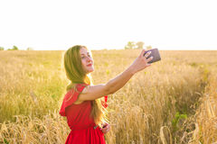 Young happy woman smiling while taking selfie picture with mobile phone in the field Stock Images
