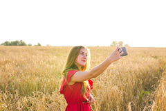 Young happy woman smiling while taking selfie picture with mobile phone in the field Royalty Free Stock Photography