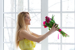 Young happy woman smiling with tulip bunch in yellow dress. Royalty Free Stock Photo