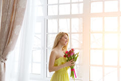 Young happy woman smiling with tulip bunch in yellow dress, sunlight Royalty Free Stock Images