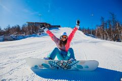 Young happy woman snowboarder sits on on a snowy mountain slope. Winter royalty free stock photography