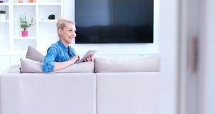 Woman on sofa using tablet computer Stock Photo