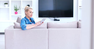 Woman on sofa using tablet computer Royalty Free Stock Photos
