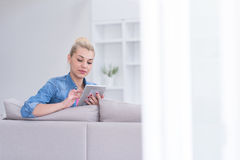 Woman on sofa using tablet computer Royalty Free Stock Images