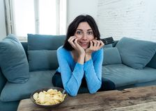 Lifestyle portrait of cheerful young woman sitting on the couch watching TV holding remote control stock images
