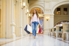Young happy woman with some shopping bags in the mall Royalty Free Stock Photos