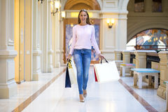 Young happy woman with some shopping bags in the mall Royalty Free Stock Photo