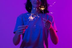 Young happy woman with sparklers. Celebrate Christmas and New Year royalty free stock images