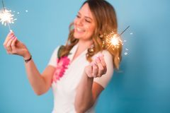 Young happy woman with sparklers celebrate and laugh on blue background stock photography