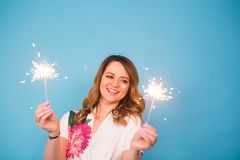 Young happy woman with sparklers celebrate and laugh on blue background royalty free stock photo
