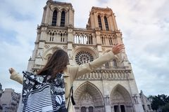 Young happy woman standing in front of the famous Notre Dame cathedral in Paris, hands raised up to the sky. Young stylishhappy woman tourist standing in front stock photography