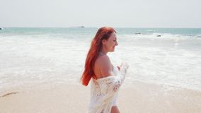 Young woman enjoys relaxing at the ocean. Young happy woman standing with hair flying on the wind on the ocean shore on a sunny day, slow motion stock footage