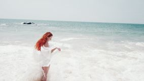 Young woman enjoys relaxing at the ocean. Young happy woman standing with hair flying on the wind on the ocean shore on a sunny day, slow motion stock video
